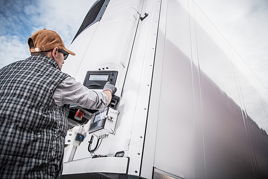 Refrigerated Semitrailer Cargo. Adjusting Temperature by Caucasian Truck Driver